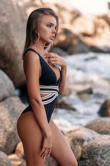 Mulher jovem e bonita de biquíni preto posando na praia rochosa