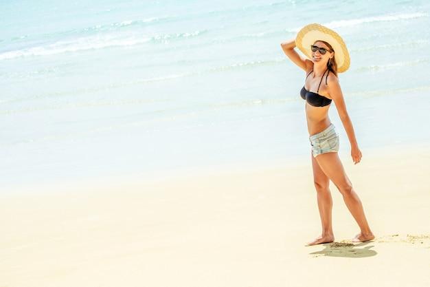 Mulher jovem e bonita de biquíni sexy em pé na praia do mar. copie o espaço