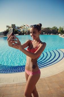Mulher jovem e bonita de biquíni tirando uma selfie à beira da piscina