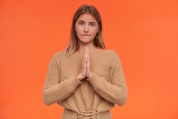 Mulher jovem e bonita de cabeça branca perplexa com maquiagem natural, levantando as mãos em gesto de oração e mordendo o lábio de forma preocupante enquanto fica de pé sobre a parede laranja