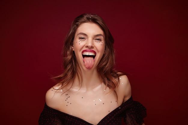 Mulher jovem e bonita de cabelo castanho alegre com maquiagem festiva usando um top preto elegante com pontos vermelhos enquanto posava, se divertindo e mostrando a língua alegremente