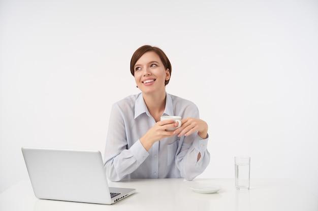 Mulher jovem e bonita de cabelo castanho bonito com um corte de cabelo curto na moda, bebendo uma xícara de chá enquanto está sentada no branco com roupas formais
