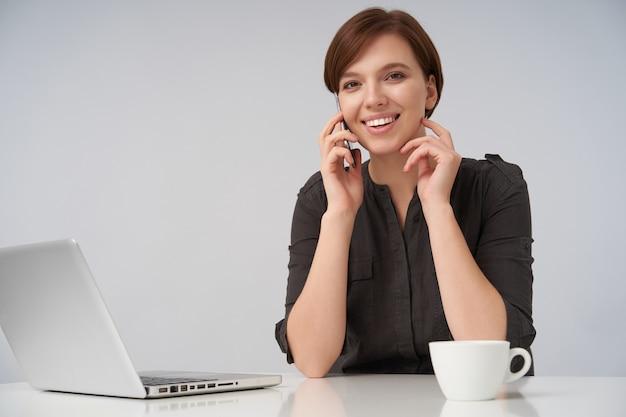 Mulher jovem e bonita de cabelo castanho com corte de cabelo curto na moda e parece positivamente com um sorriso encantador enquanto conversa ao telefone em branco