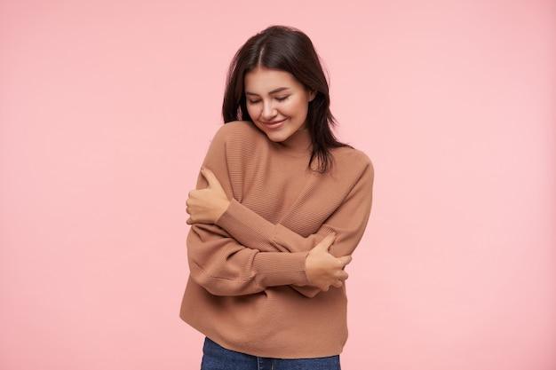 Mulher jovem e bonita de cabelo castanho com penteado casual, abraçando-se e sorrindo bem em pé sobre uma parede rosa em um suéter de malha marrom