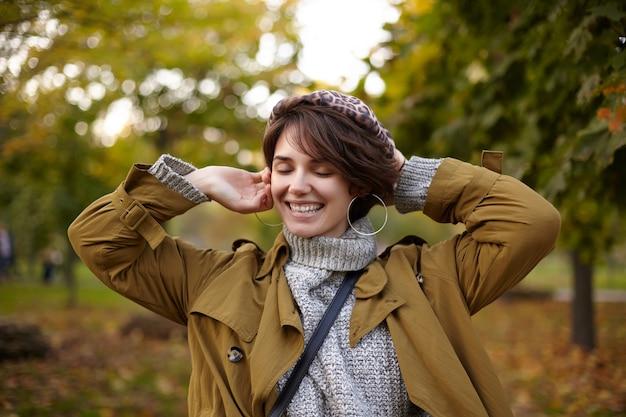 Mulher jovem e bonita de cabelo castanho positivo com penteado casual, mantendo os olhos fechados enquanto sorri alegremente, em pé sobre árvores amareladas no parque da cidade