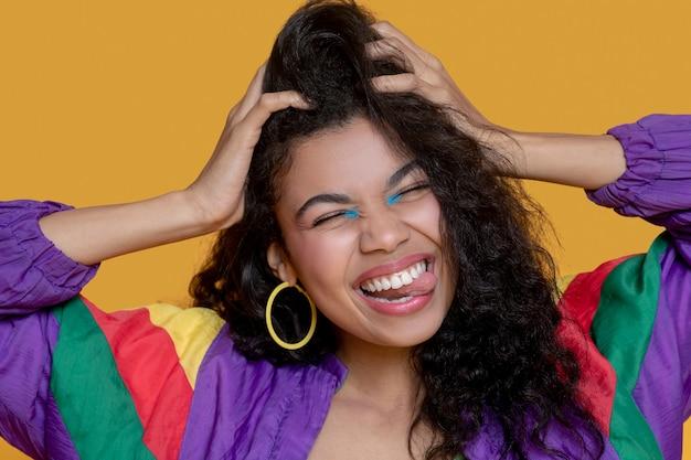 Mulher jovem e bonita de cabelo escuro em jaqueta brilhante sorrindo feliz