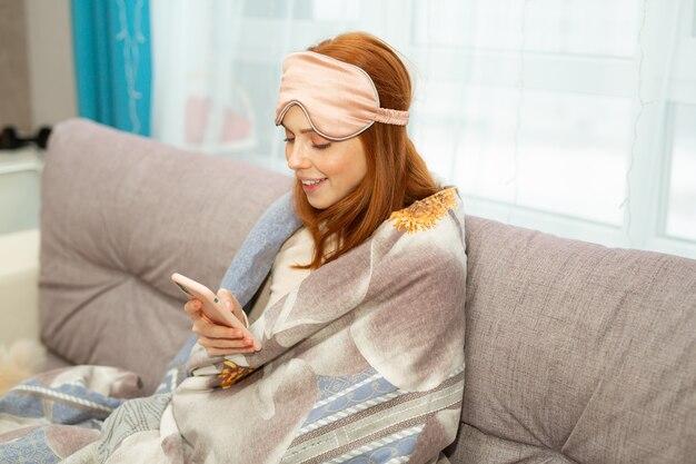 Mulher jovem e bonita de cabelo vermelho sentada no sofá, debaixo das cobertas, com um telefone celular