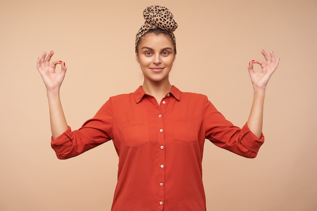 Mulher jovem e bonita de cabelos castanhos com bandana, sorrindo levemente enquanto olha para frente e dobrando os dedos em um gesto de mudra, isolado sobre uma parede bege
