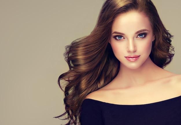 Mulher jovem e bonita de cabelos castanhos com cabelo volumoso e esvoaçante. linda modelo com penteado longo, denso e reto e maquiagem viva. arte para cabeleireiro, cuidados com os cabelos e produtos de beleza.