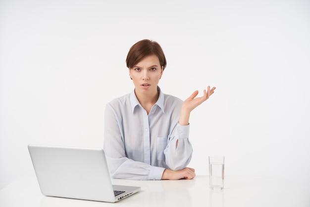 Mulher jovem e bonita de cabelos castanhos séria com corte de cabelo curto da moda, franzindo a testa franzindo as sobrancelhas e mantendo a palma da mão levantada enquanto está sentado à mesa no branco