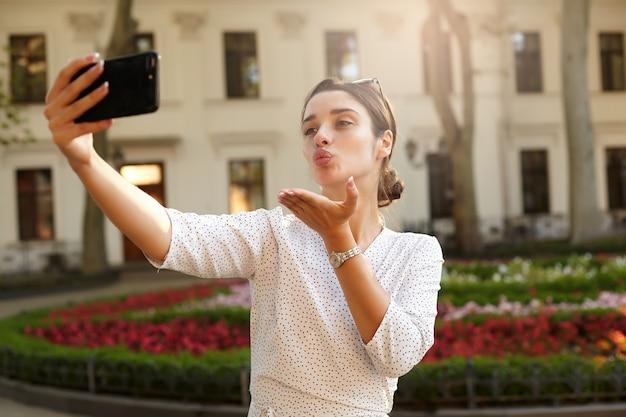 Mulher jovem e bonita de cabelos escuros com penteado casual posando ao ar livre em um dia quente de primavera com o celular na mão levantada, mandando um beijo no ar enquanto faz uma foto de si mesma