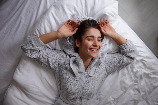 Mulher jovem e bonita de cabelos escuros de aparência agradável deitada na cama com roupas cinza casuais, sorrindo sinceramente com as mãos levantadas e mantendo os olhos fechados, isolada no interior da casa
