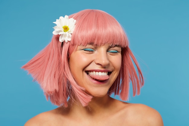 Mulher jovem e bonita de cabelos rosa com maquiagem colorida se divertindo, mostrando feliz a língua e mantendo os olhos fechados
