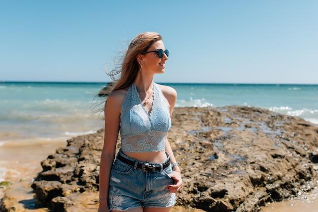 Mulher jovem e bonita de chapéu na praia