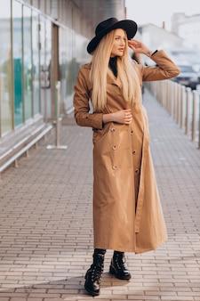 Mulher jovem e bonita de chapéu preto e casaco bege caminhando pelo shopping