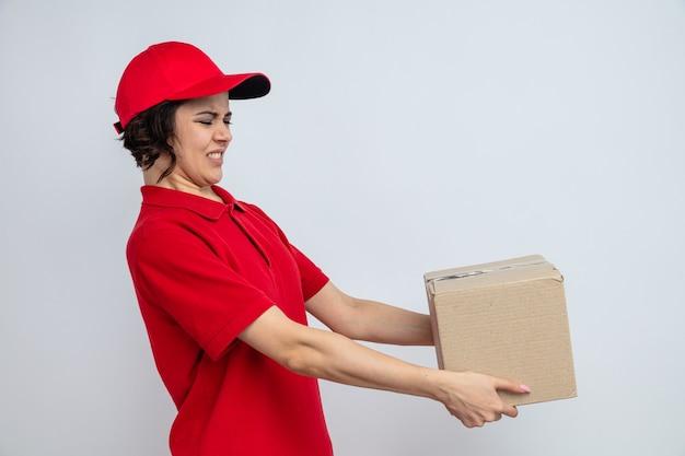Mulher jovem e bonita de entrega descontente segurando e olhando para uma caixa de papelão
