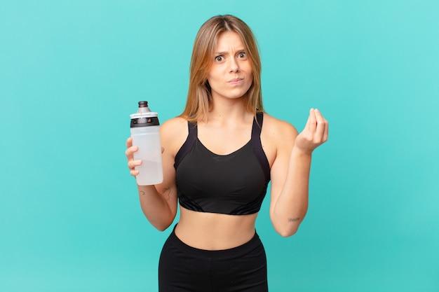 Mulher jovem e bonita de fitness fazendo capice ou gesto de dinheiro, dizendo para você pagar