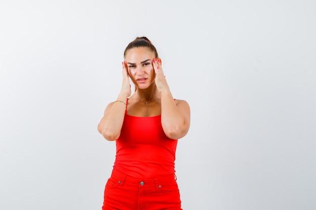 Mulher jovem e bonita de mãos dadas nas têmporas em uma blusa vermelha, calças e parecendo cansada. vista frontal.