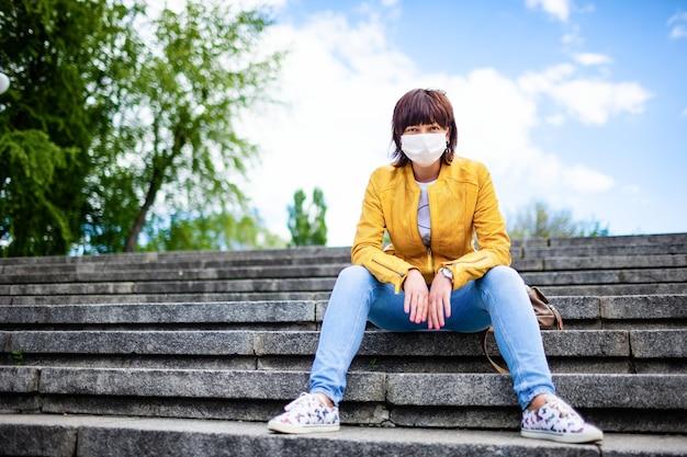 Mulher jovem e bonita de meia-idade com máscara médica branca e roupas casuais sentada nos degraus do parque da cidade em um dia quente de primavera