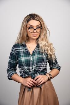 Mulher jovem e bonita de óculos e posando.