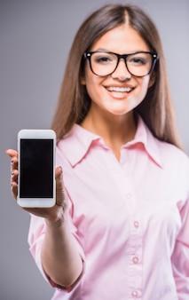Mulher jovem e bonita de óculos, segurando o telefone inteligente.