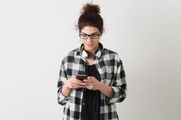 Mulher jovem e bonita de óculos, segurando smartphone, usando dispositivo digital, sorrindo, feliz, fones de ouvido, isolado no fundo branco, camisa quadriculada, estilo hippie, estudante, digitando mensagem