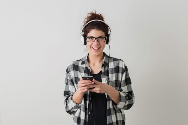 Mulher jovem e bonita de óculos, usando smartphone, emocional, rindo, positiva, feliz, ouvindo música em fones de ouvido, isolada, camisa quadriculada, estilo hippie, estudante, olhando na câmera