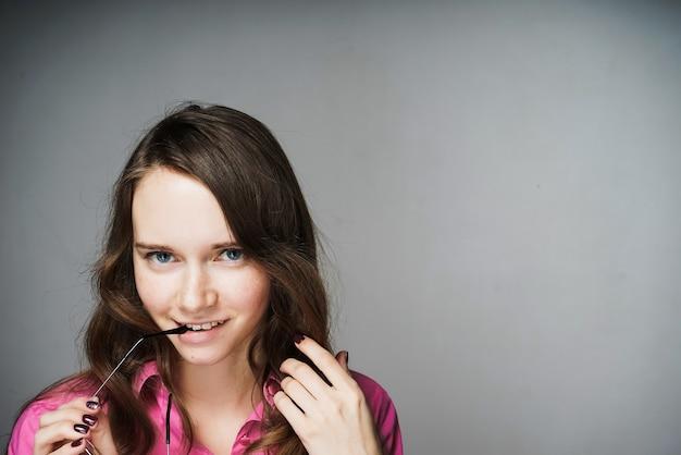 Mulher jovem e bonita de olhos azuis, trabalhador de escritório com uma camisa rosa e óculos nas mãos.