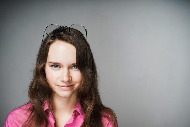 Mulher jovem e bonita de olhos azuis, trabalhadora de escritório, com uma camisa rosa, olha para a câmera e sorri