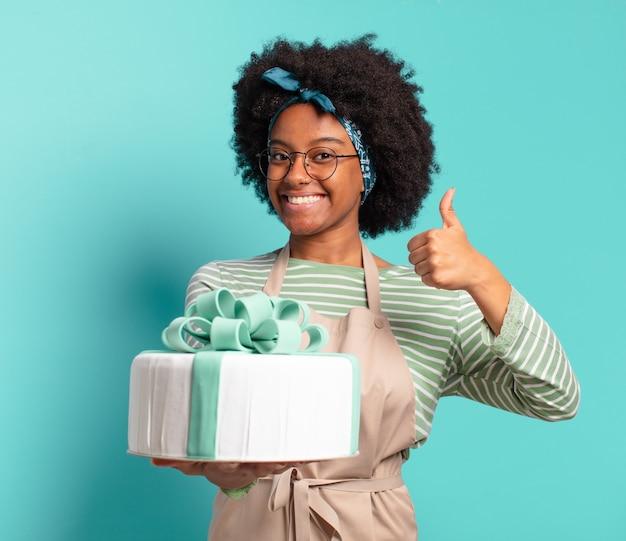 Mulher jovem e bonita de padeiro afro com um bolo de aniversário