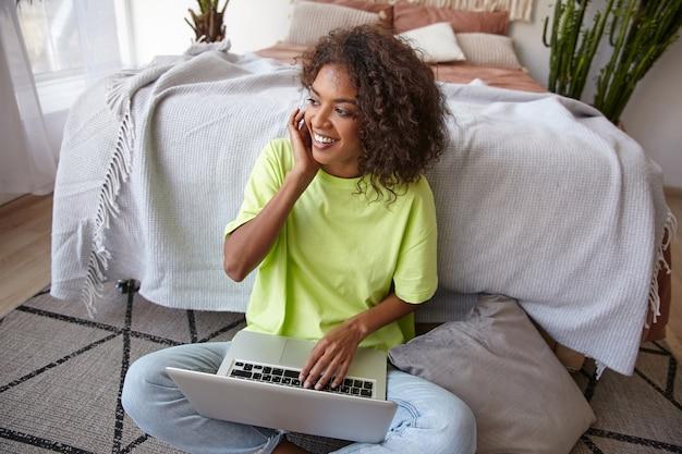 Mulher jovem e bonita de pele escura com cachos castanhos, sorrindo feliz e colocando o cabelo atrás da orelha, trabalhando em casa com o laptop no quarto de dormir
