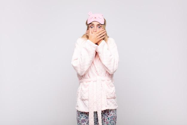 Mulher jovem e bonita de pijama, cobrindo a boca com as mãos com uma expressão chocada e surpresa, mantendo um segredo ou dizendo oops