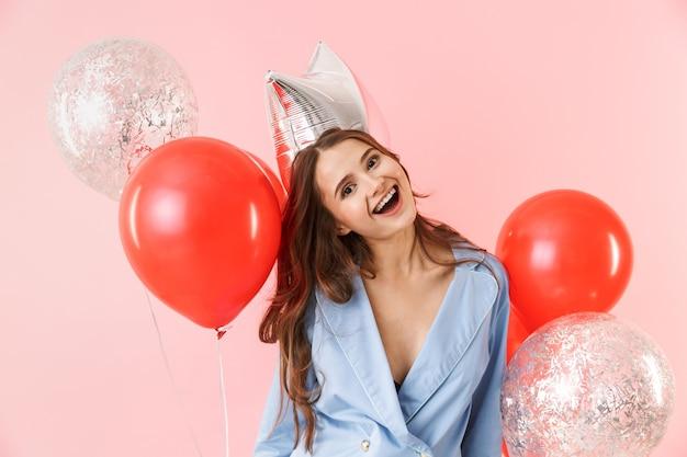 Mulher jovem e bonita de pijama em pé, isolada sobre um fundo rosa, comemorando com balões