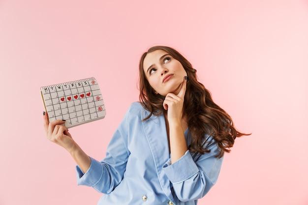 Mulher jovem e bonita de pijama em pé, isolada sobre um fundo rosa, mostrando o calendário menstrual