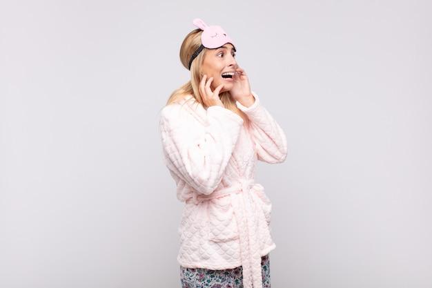 Mulher jovem e bonita de pijama, feliz, animada e surpresa, olhando para o lado com as duas mãos no rosto