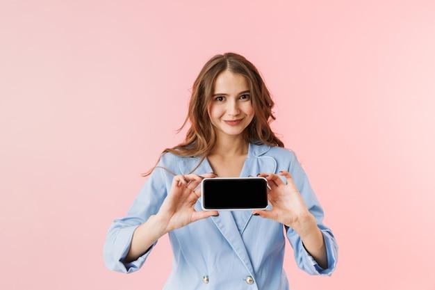 Mulher jovem e bonita de pijama isolada sobre fundo rosa, mostrando tela em branco do celular