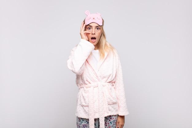 Mulher jovem e bonita de pijama, parecendo chocada, assustada ou apavorada, cobrindo o rosto com a mão e espiando por entre os dedos