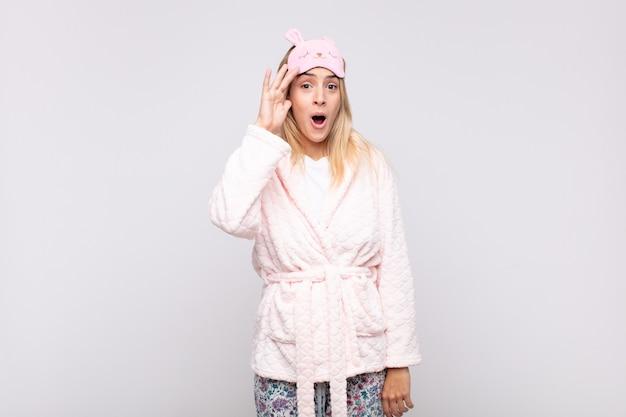 Mulher jovem e bonita de pijama, parecendo feliz, atônita e surpresa, sorrindo e percebendo boas notícias incríveis e incríveis
