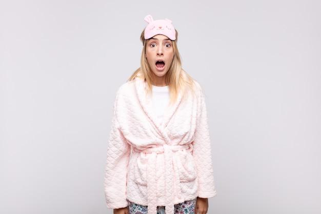 Mulher jovem e bonita de pijama, parecendo muito chocada ou surpresa, olhando com a boca aberta dizendo uau