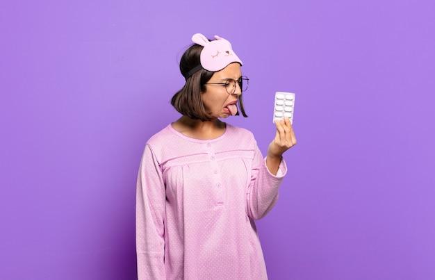 Mulher jovem e bonita de pijama segurando comprimidos