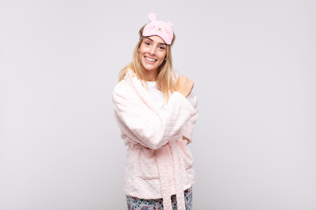 Mulher jovem e bonita de pijama, sentindo-se feliz, positiva e bem-sucedida, motivada para enfrentar um desafio ou comemorar bons resultados