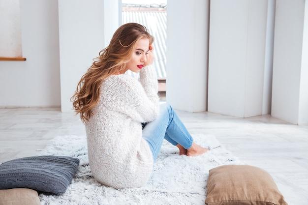Mulher jovem e bonita de suéter sentada no tapete e bebendo chá em casa