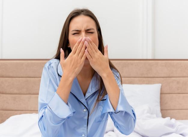 Mulher jovem e bonita decepcionada de pijama azul, sentada na cama, sentindo o cansaço matinal, bocejando, cobrindo a boca com as mãos no interior do quarto sobre fundo claro