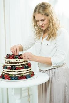 Mulher jovem e bonita decora um bolo de três níveis com bagas