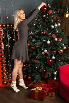 Mulher jovem e bonita decora uma árvore de natal com bolas no interior da casa de ano novo. - imagem
