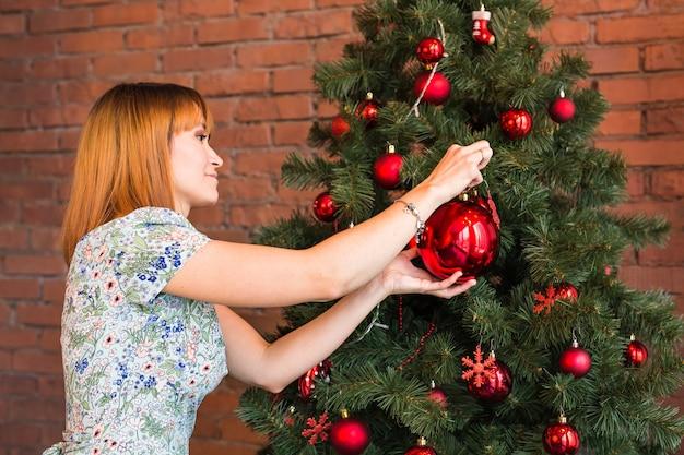 Mulher jovem e bonita decorando a árvore de natal