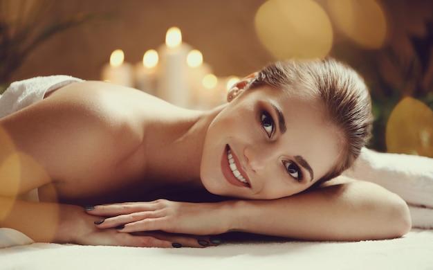Mulher jovem e bonita deitada e esperando sua massagem. conceito de spa