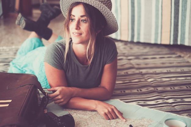 Mulher jovem e bonita deitada no tapete e apontando no atlas. jovem de chapéu, planejamento de localização no mapa para férias. mulher pensativa, sonhando acordada com seus planos de viagem enquanto aponta no mapa