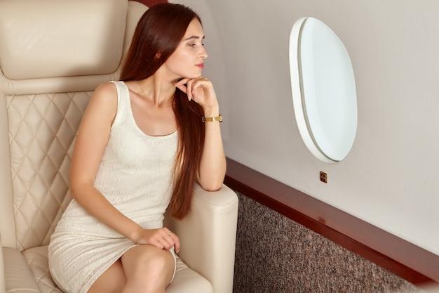 Mulher jovem e bonita dentro de um avião.
