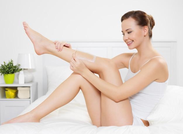 Mulher jovem e bonita depilando a pele das pernas com cera está no quarto
